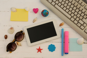 Keyboard, post it note, label tag, sunglasses, pen and tablet computer on white background