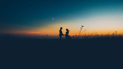 silhouette of couple with sunset background
