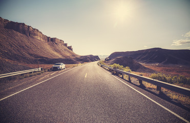 Retro toned desert highway against sun, travel concept