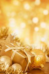 Golden Christmas decorations in front of defocused lights