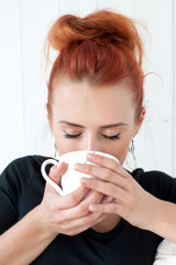 beautiful, young, red-haired woman drinking coffee from a mug in his hand. Lifestyle, peace, home, rest, relax