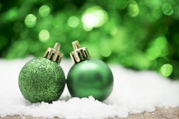 Green Christmas balls on snow against green bokeh background