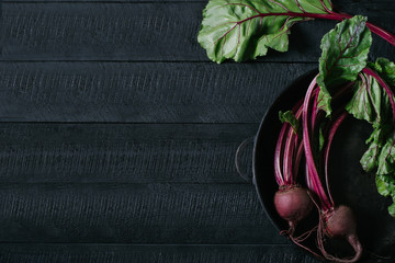 Beets with tops in round metal pan on a black wooden background with a free space top view