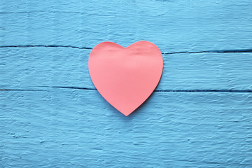 Blank pink paper note with heart shape on grunge blue wooden background with copy space
