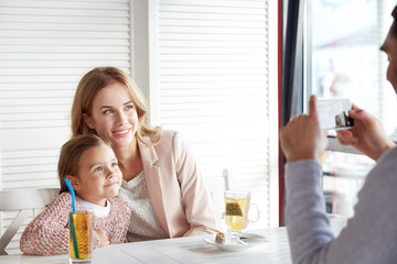 happy family picturing by smartphone at restaurant