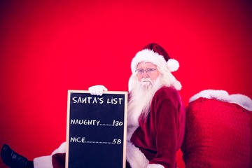Composite image of santa sits leaned on his bag with a board