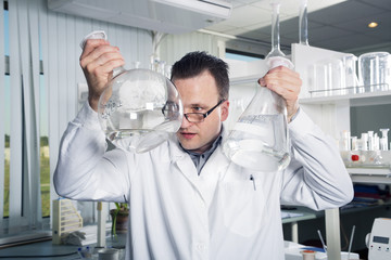 Laboratory assistant looking in a bottle with liquid