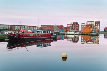 boat and colorful buildings on water at sunrise