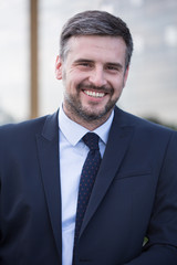 Smiling businessman in black suit