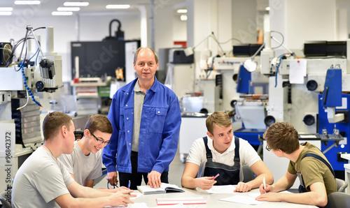Meister in der Berufsausbildung mit Azubis im Bereich Metallverarbeitung- CNC Technik