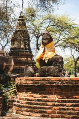 Ancient Buddha statue with shiny yellow robe, in Ayutthaya, Thai