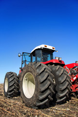 Fototapete - Powerful agricultural tractor in a field