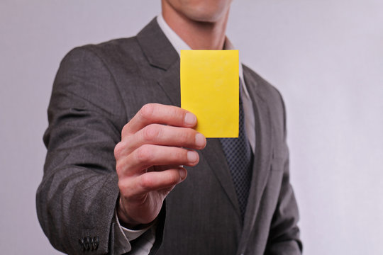 Close up of Businessman showing yellow card. Business and finance concept