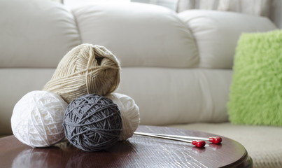 Several balls of wool lying on a table with knitting needles