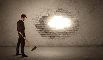 Business man hitting brick wall with hammer and opening a hole