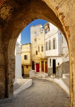 Narrow street in Tangier, view through the town wall gate, Morocco