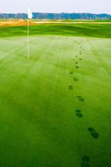 footprints on golf grass near flag in dew