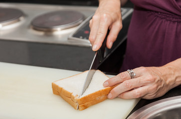 Closeup of a hand which a sandwich cut with the knife. A mother prepares sandwich for school or breakfest.