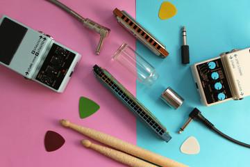 Music concept - guitar pedals, drum sticks, harmonica, audio plug, guitar slide and guitar picks on half blue half pink background