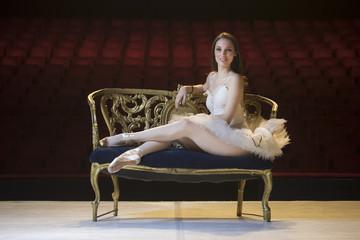 Young ballerina in theater posing, in costume, dancing
