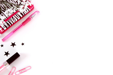 A white background styled desktop with pink and black paper clips, lipstick, stars, and a zebra striped notebook.