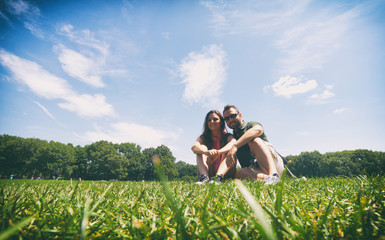 Couple sitting on the grass in Central Park, New York City.
