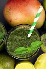 Green healthy juice with fruits and mint on table close up