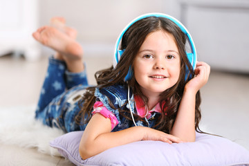 Little girl with headphones in the room