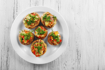 A plate with stuffed mushrooms on wooden background, top view
