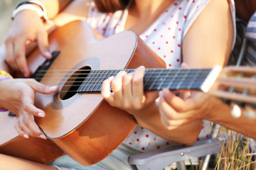 Attractive couple playing guitar, outdoors, close up