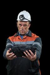 Coal miner showing lump of coal