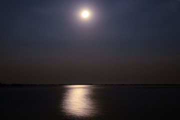 Golden Moon and its reflection in the sea at night