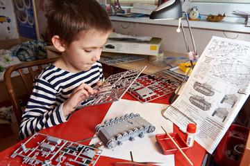 Little boy collects plastic model tank