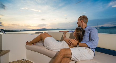 Romantic vacation . Beautiful couple  looking in sunset  from the yacht