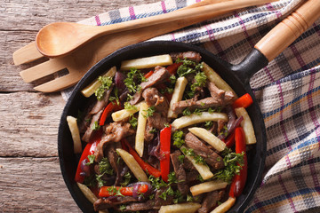 Peruvian Food: Lomo saltado closeup in a frying pan. horizontal top view