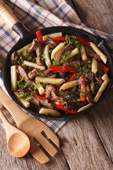 Homemade Peruvian cuisine: lomo saltado in a pan close-up vertical
