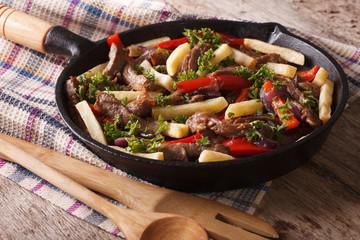 Homemade Peruvian cuisine: lomo saltado in a pan close-up horizontal