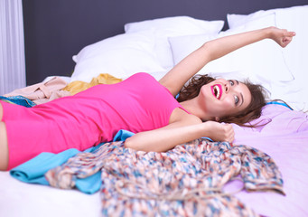 Happy woman lying bed surrounded by her clothes