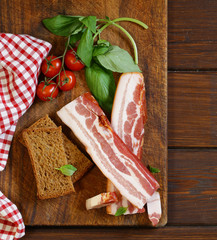 smoked bacon with basil and tomatoes on a cutting board
