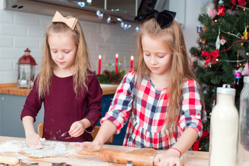 Adorable girls baking gingerbread cookies for Christmas at home kitchen