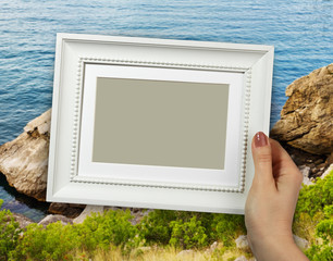 Wooden frame in woman hands on the background Sea view
