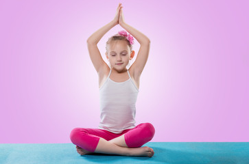 Little girl sitting in yoga pose over color background.