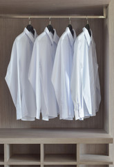 Classic white shirts in warm wooden wardrobe