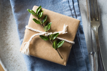 Detail of place setting: simply wrapped present decorated with green branch and twine on the blue napkin