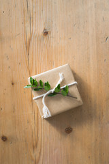 A small present wrapped with kraft paper and decorated with evergreen plant and twine. Wooden backgrounds