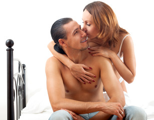 Middle-aged couple kissing on white sheet in bed