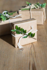 Simple gift wrapping idea: kraft paper, evergreen plants and twine. Selective focus