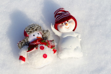 two Snowman lying on the snow