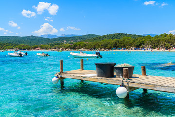 Wooden jetty and azure sea water of Santa Giulia bay, Corsica island, France