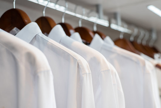 row of white shirts hanged in closet (soft focus)